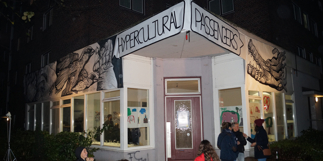 """Eine Hausecke mit einer Eingangstür, die in den Projektraum von """"Hypercultural Passengers"""" führt. Ein paar Menschen stehen davor und unterhalten sich. Über der Tür ist ein Banner angebracht, auf dem schwarz-weisse Zeichungen zu sehen sind und der Schriftzug """"Hypercultural Passengers""""."""