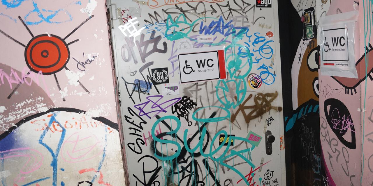 Das Bild zeigt die Tür der barrierfreien Toilette. Zwei Schilder mit Rollstuhl-Signet weisen darauf hin. Die Tür und die Wand sind mit Graffitti verziert.
