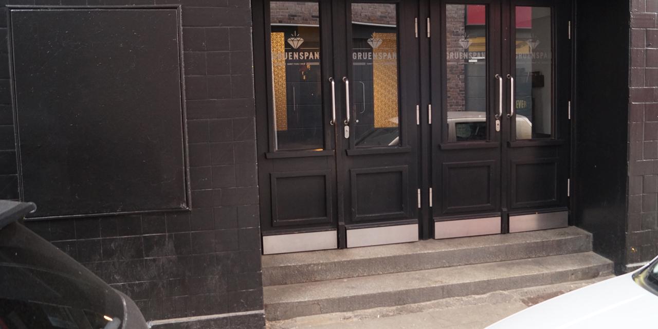 """Zu sehen ist der Eingang zum Veranstaltungsort """"Grünspan"""". Zwei Stufen führen hoch zu 2 Glasflügeltüren."""
