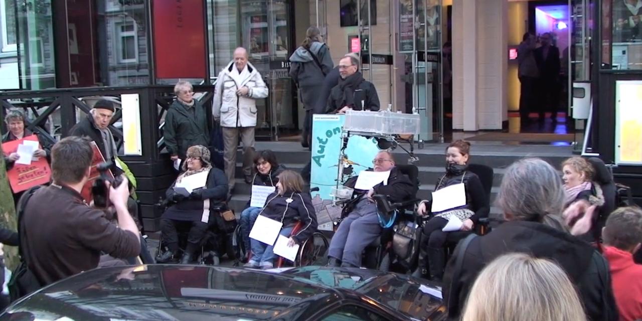 Mehrere Rollstuhlfahrer stehen vor den Stufen des Eingangs zu den Hamburger Kammerspielen, Sie haben Schilder, die gegen die fehlende Barrierefreiheit protestieren.