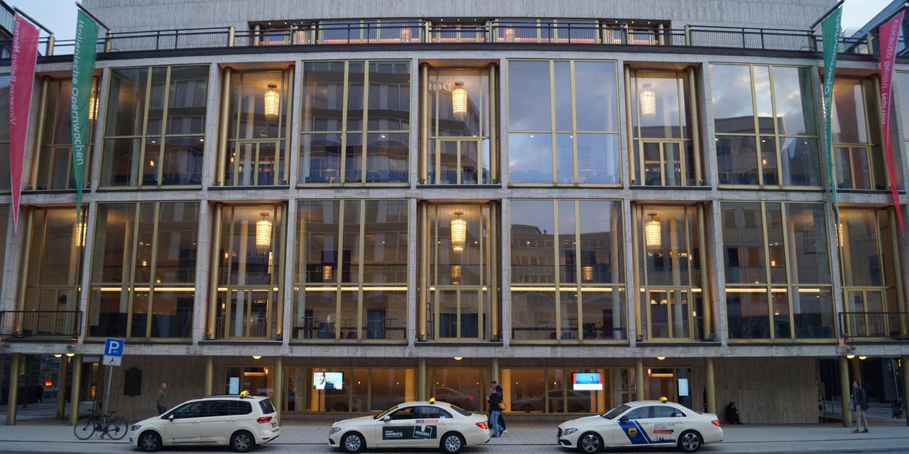 Zu sehen ist die Außenfassade der Hamburger Staatsoper, sie besteht hauptsächlich aus Fenstern. Davor stehen 3 Taxis.