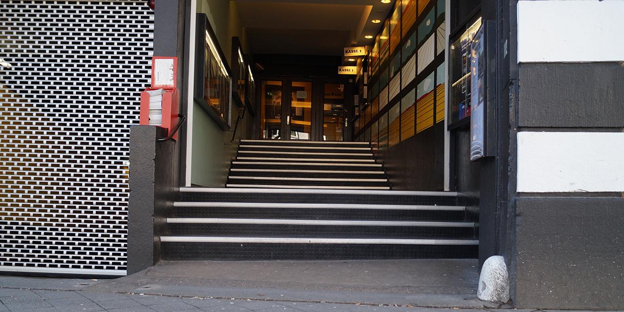 Der Eingang des Abaton-Kinos. 3 mal 4 Stufen führen hoch zur Kasse und zum Eingang des Kinos. Durch die Zwischenpodeste ist der Gang bis oben etwa 10 Meter lang.