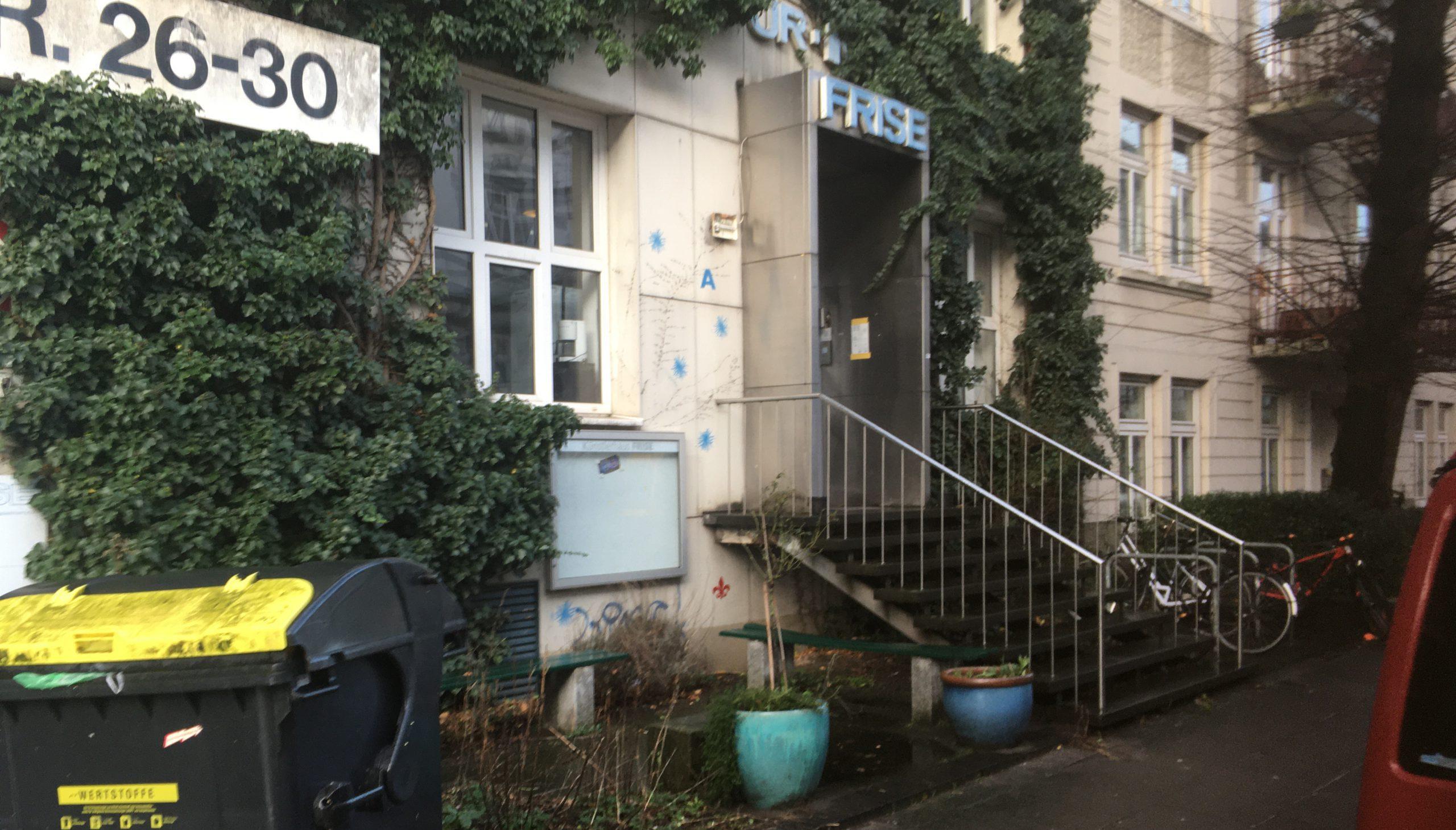 Zu sehen ist der Eingang des Künstlerhauses FRISE in Altona. Eine Treppe mit 8 Stufen führt zum Eingang hinauf. Im Vordergrund stehen 2 Blumenkübel und eine Mülltonne.