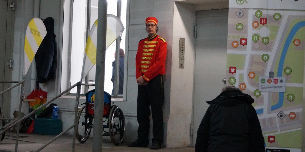 Auf einem Podest steht ein Mann in der Uniform eines Fahrstuhl-Führers vor der Tür eines Lastenfahrstuhles. Neben ihm steht ein Rollstuhl und vorne im Bild steht ein Aufsteller der einen Stadtplan zeigt, auf dem verschiedene Symbole für barrierefreie und nicht-barrierefrei mit dem Rollstuhl zu erreichende Orte zu sehen sind.